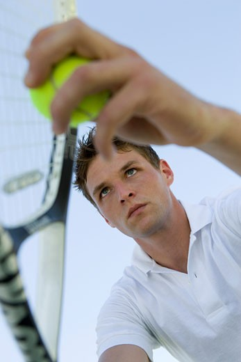 Young man with tennis racket on tennis court, low angle view : Stock Photo