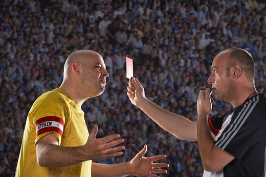 Referee holding up red card to player, side view : Stock Photo