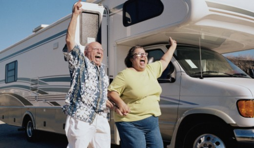Senior couple celebrating by camper van, arms raised : Stock Photo