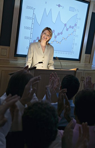 Businesspeople Applauding a Speaker at a Podium During a Business Presentation : Stock Photo