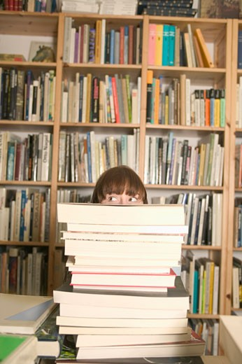 Young woman looking to one side over pile of books obscuring face : Stock Photo