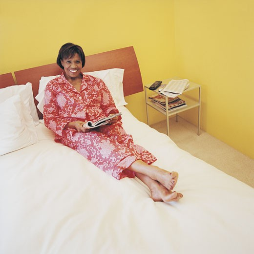 Portrait of a Mature Woman Lying on a Bed Reading a Magazine : Stock Photo