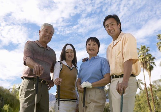 Portrait of Four Smiling People Standing on a Golf Course : Stock Photo