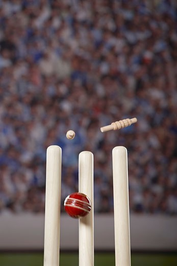 Ball hitting cricket stumps on, bails flying, close up : Stock Photo