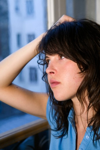 Young woman with hand on head, looking away, close-up : Stock Photo
