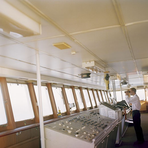 Captain Standing at a Ship's Helm Looking Out the Window With Binoculars : Stock Photo
