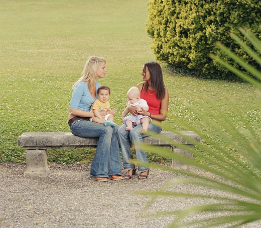 Two young women with baby boys (6-8 months) on park bench : Stock Photo