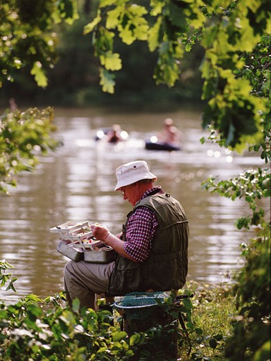 Senior man sitting on riverbank, holding tackle box, side view : Stock Photo