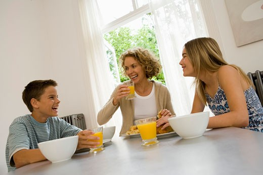 Mother having breakfast with son and daughter (13-15) smiling : Stock Photo