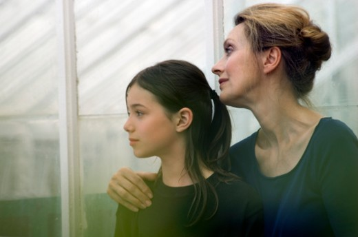Stock Photo: 1598R-9968559 Girl (9-11) and grandmother looking out greenhouse window, profile
