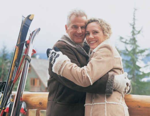 Portrait of a Smiling, Mature Couple Embracing on the Wooden Balcony of Their Chalet : Stock Photo