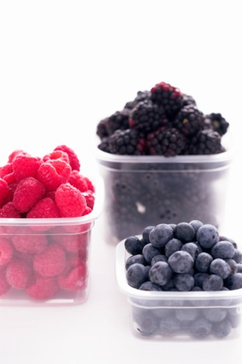 Blueberries, raspberries and blackberries in plastic containers : Stock Photo