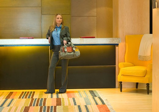 Woman wearing suit, standing at reception of modern hotel, portrait : Stock Photo