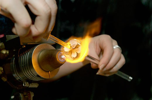Woman using torch to make glass marble : Stock Photo
