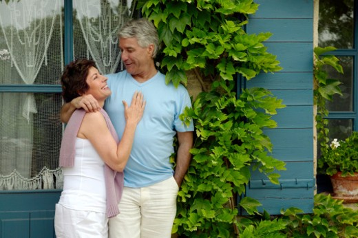 Stock Photo: 1598R-9969123 Mature Couple Standing Close Together In Front of a Cottage