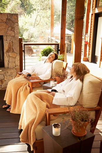 Two young women in bathrobes with mugs sitting on armchairs at spa : Stock Photo
