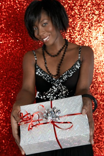 Young woman holding gift box, smiling, portrait : Stock Photo