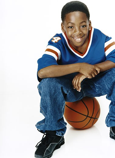 Portrait of a Young, Smiling Boy Wearing a Sports Strip and Sitting on Top of a Basketball : Stock Photo