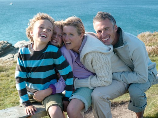 Family with two children (7-10) hugging on bench at ocean : Stock Photo