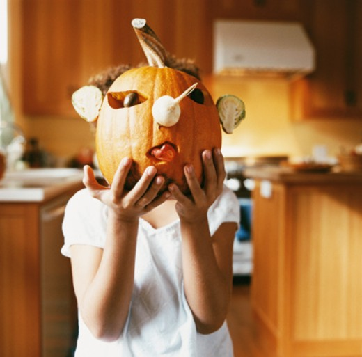 Stock Photo: 1598R-9971591 Portrait of a Girl Holding a Jack O Lantern Pumpkin In Front of Her Face