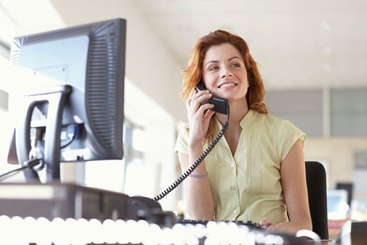 Young businesswoman using telephone at desk, smiling : Stock Photo