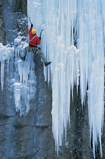 Rear View of An Adult Using An Ice Axe to Ascend An Icy Rock Face : Stock Photo