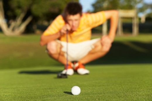 Stock Photo: 1598R-9971896 Teenage boy (16-17) sighting putt on green, focus on golf ball