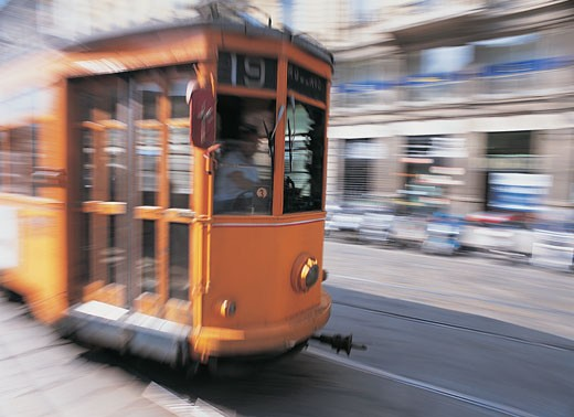Stock Photo: 1598R-9972035 Tram Moving Through a City Road