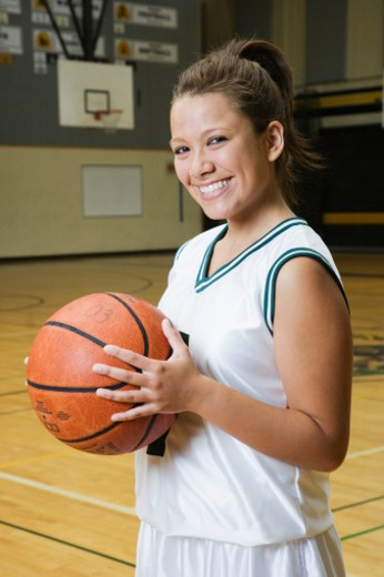 Teenage girl (14-16) holding basketball, smiling, portrait : Stock Photo