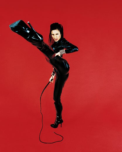 Portrait of a Dominatrix Holding a Whip and Standing on one Leg : Stock Photo