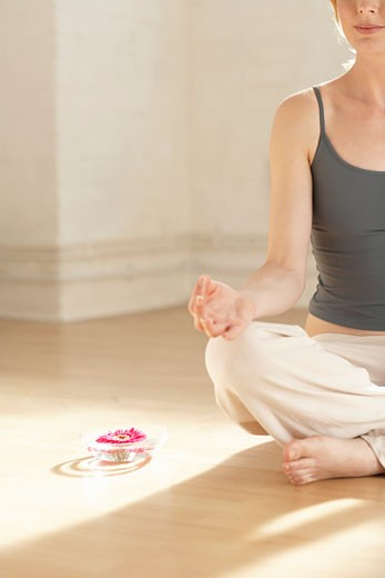 Stock Photo: 1598R-9972704 Woman sitting in meditation by flower in bowl