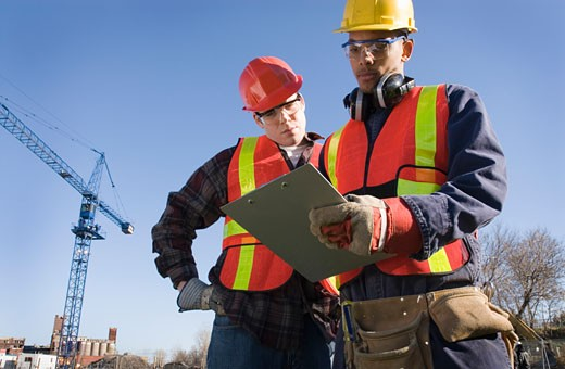 Two male construction workers looking at folder, crane in background : Stock Photo