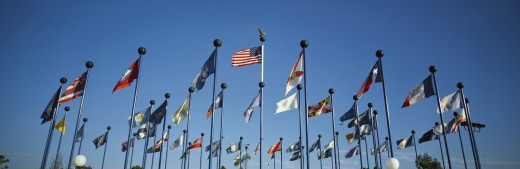 Stock Photo: 1598R-9973478 'There are 50 State Flags waving in the wind on flagpoles equal distant apart against a blue sky, with the American flag in the center. These are located at Sea World.'