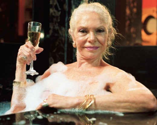 Stock Photo: 1598R-9973512 Mature woman relaxing in hot tub, holding champagne flute, portrait