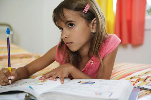 Girl (8-10) doing home-work on bed : Stock Photo