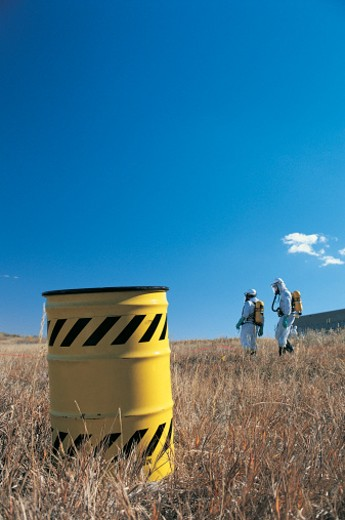 Workers with chemical waste drum : Stock Photo