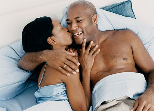 Overhead View of a Woman Kissing a Man in Bed : Stock Photo