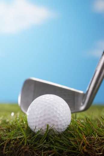 Golf club against golf ball, ground view, close up : Stock Photo