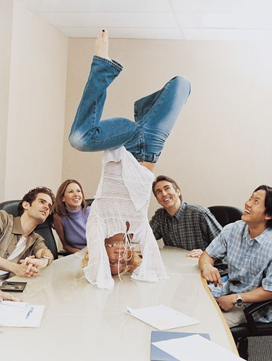 Businesswoman Doing a Handstand on a Table in a Conference Room to the Amusement of Her Colleagues : Stock Photo