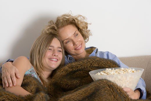 Stock Photo: 1598R-9974437 Mother and daughter (13-15)  on sofa with bowl of popcorn, smiling