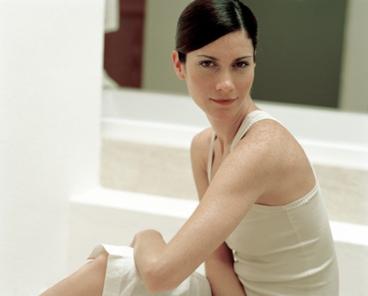 Young woman sitting in bathroom, portrait : Stock Photo