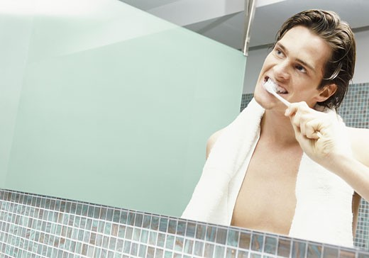 Reflection in a Bathroom Mirror of a Young Man Brushing His Teeth : Stock Photo