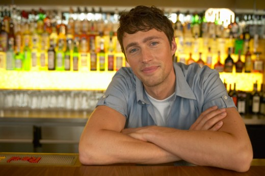 Stock Photo: 1598R-9974920 Man working in bar, leaning on bar with folded arms, portrait