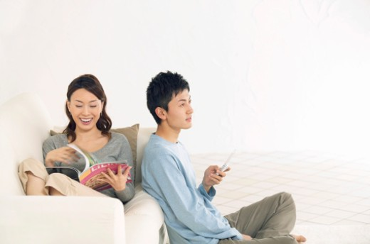 Stock Photo: 1598R-9974925 Woman Sits on a Sofa Reading a Magazine and Laughing, Her Boyfriend Sitting on the Floor Using His Mobile Phone
