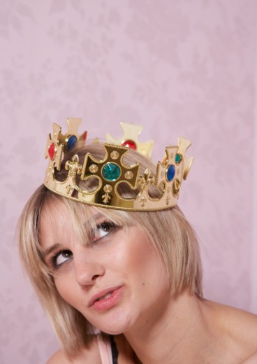 Young woman wearing crown, looking up, close-up : Stock Photo
