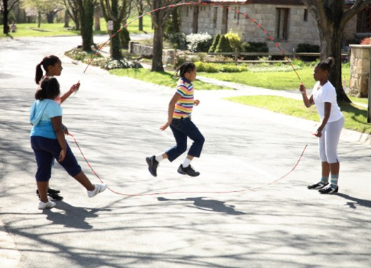 Stock Photo: 1598R-9975372 Girls (9-13) playing with jumping rope in street