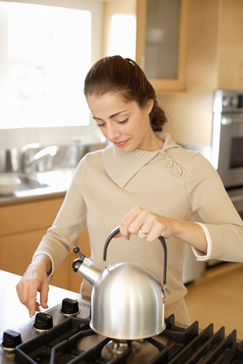 Young woman putting kettle on stove, close-up : Stock Photo