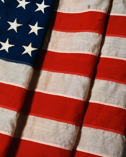 Stock Photo: 1598R-9975849 This is a vertical view of a folded American flag. It is a vintage flag with 48 stars. It is folded twice with one fold cutting into the field of stars and the other three quarters into the red and white stripes.