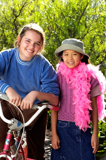 Stock Photo: 1598R-9976116 Girls (9-12) with bicycle, smiling, portrait