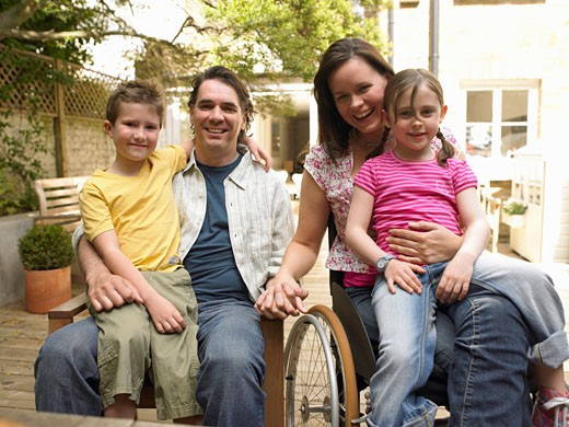 Family sitting in garden, woman in wheelchair, smiling, portrait : Stock Photo